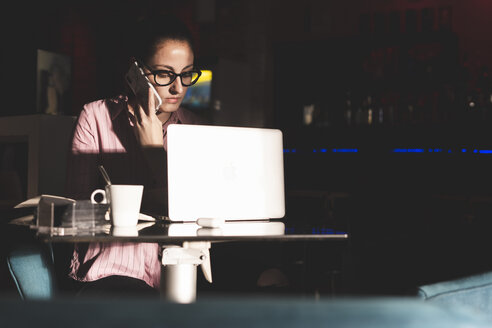 Woman working long hours, sitting in a coffee shop - ERRF00351