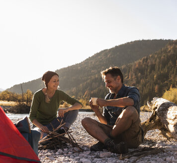 Mature couple camping at riverside in the evening light - UUF16271