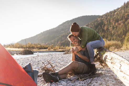 Mature couple camping at riverside in the evening light - UUF16274
