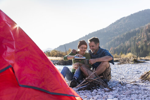 Mature couple camping at riverside in the evening light - UUF16280
