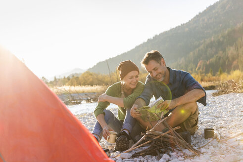 Mature couple camping at riverside, looking on map - UUF16283