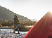 Mature couple camping at riverside in the evening light - UUF16295