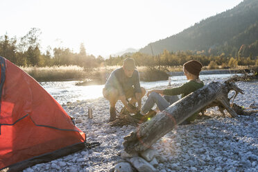 Mature couple camping at riverside, collecting wood for a camp fire - UUF16301