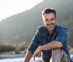 Mature man camping at riverside - UUF16307