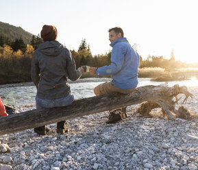 Mature couple camping at riverside in the evening light - UUF16310