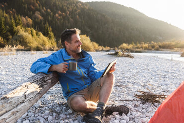 Mature man camping at riverside, using tablet - UUF16316