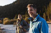 Mature couple hiking at riverside in the evening light - UUF16319