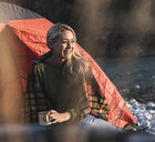 Mature woman camping, sitting in front of tent - UUF16322