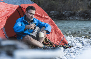 Mature man camping at riverside, espresso maker and cup - UUF16325