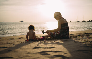 Thailand, Koh Lanta, mother playing with little daughter on the beach by sunset - GEMF02653