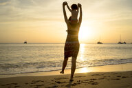 Thailand, Koh Lanta, back view of mother with baby girl on her shoulders at seashore during sunset - GEMF02656