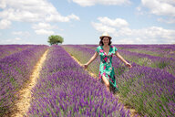 France, Provence, Valensole plateau, smiling woman walking among lavender fields in summer - GEMF02663