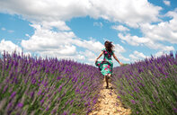 France, Provence, Valensole plateau, back view of woman running among lavender fields in summer - GEMF02669