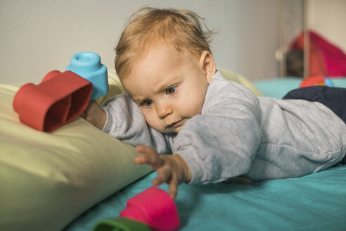 Portrait of baby girl lying on bed playing with plastic toy - MOMF00560