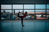 A woman exercising by a glass window - INGF09929