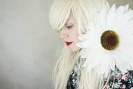 A young blonde woman with blonde hair posing with a huge daisy - INGF10046