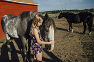 Side view of girl stroking horse while standing at barn - CAVF59905