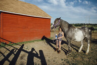 Girl holding spray bottle while standing by horse at barn - CAVF59908