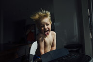 Portrait of shirtless boy sticking out tongue while enjoying breeze from air conditioner at home - CAVF59917