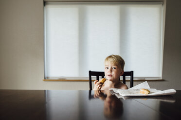 Portrait of shirtless boy eating bread while sitting on chair at home - CAVF59920