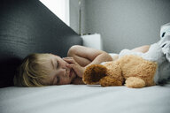 Shirtless boy with toy sleeping on bed at home - CAVF59926