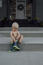 Shirtless baby boy wearing boots while sitting on steps - CAVF59929