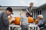 Father with kids cutting pumpkin at table in backyard during Halloween - CAVF59959