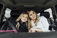 Portrait of mother and daughter sitting in car - CAVF59962