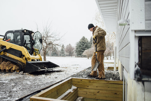 Side view of man holding shovel working in backyard against sky during winter - CAVF59974