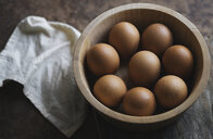 High angle view of brown eggs in bowl with napkin on wooden table - CAVF59989