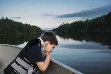 Side view of boy wearing life jacket while sitting in boat on lake - CAVF59992