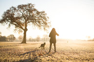 A woman with her dog in a field - INGF10392