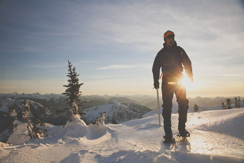 Full length of hiker with ice axe mountaineering on snowcapped mountains against sky during sunset - CAVF60120