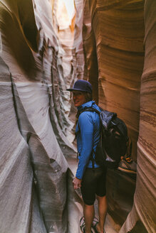 Portrait of female hiker with backpack standing amidst narrow canyons - CAVF60144