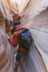 Rear view of hiker with backpack canyoneering amidst canyons - CAVF60150