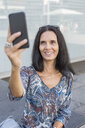 Portrait of smiling mature woman taking selfie with smartphone - JUNF01572
