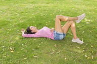 Mature woman relaxing on a meadow in summer - JUNF01587