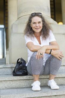 Portrait of smiling mature woman sitting on stairs in summer - JUNF01602