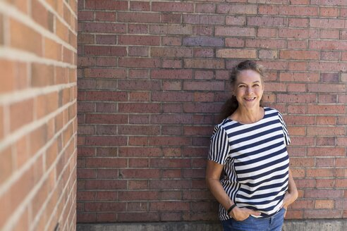 Portrait of smiling mature woman leaning against brick wall in summer - JUNF01614