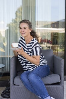 Portrait of smiling mature woman with cup of coffee sitting on lounge chair outdoors - JUNF01620