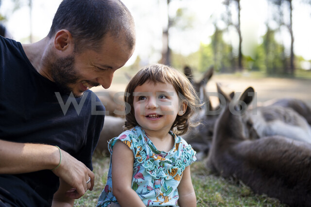 Australia, Brisbane, laughing father with his little daughter in front of  group of kangaroos - GEMF02685 - Gemma Ferrando/Westend61