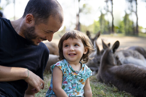 Australia, Brisbane, laughing father with his little daughter in front of  group of kangaroos - GEMF02685