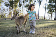 Australia, Brisbane, little girl stroking  tame kangaroo - GEMF02688