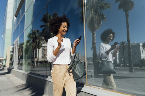 Young casual businesswoman using smartphone in the city - BOYF01240