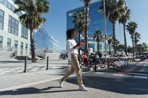 Young casual businesswoman in the city, using smartphone and crossing road - BOYF01246