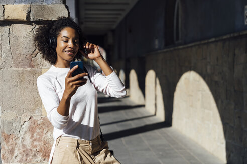 Young casual businesswoman with smartphone and earphones in the city - BOYF01255