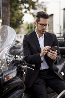 Businessman at motor scooter in the city using cell phone - MAUF01933