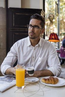Businessman having breakfast in a cafe - MAUF01954