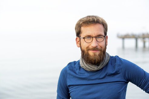 Germany, Rerik, portrait of bearded man in front of the sea wearing metal-rimmed spectacles - PUF01348