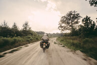 Rear view of biker wearing crash helmet while riding motorcycle on dirt road against sky - CAVF60362